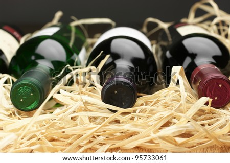 Close-up of three various wine bottles lying on straw. - stock photo