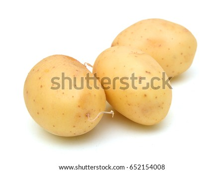Close up of three yellow potatoes against white background.