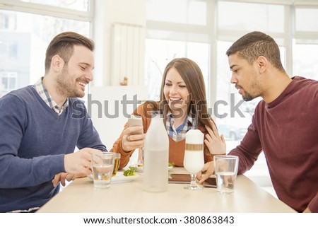 Close-up of three young cheerful people.Friends smiling and sitting in a cafe, drinking coffee and enjoying together.