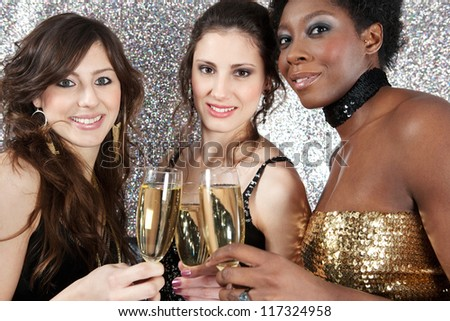 Close up of three young women toasting with champagne at a party against a silver glitter background, smiling.