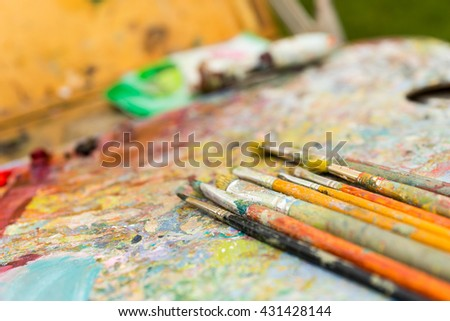 Close up of time-worn paintbrushes on an old colorful palette - stock photo