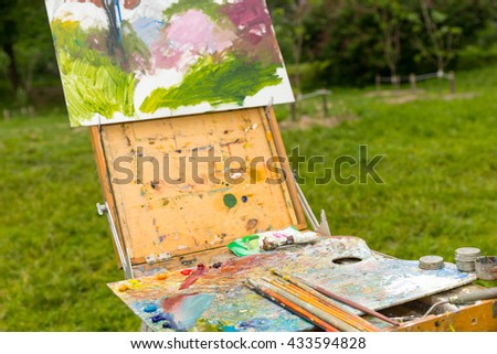 Close up of time-worn professional painter's sketchbook  with different artist's equipment colorful palette paletteknife paints and paintbrushes outdoors - stock photo