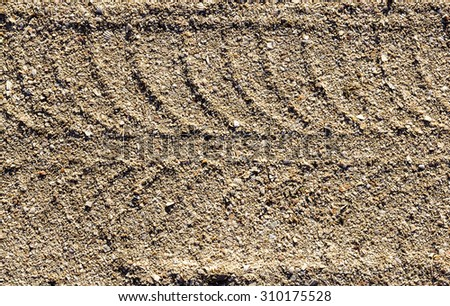close up of tire tracks in sand - stock photo