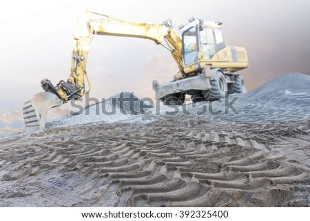 Close up of tire tracks on building site, excavator in background