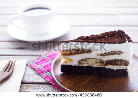 Close up of Tisamisu layer cake on a wooden plate.