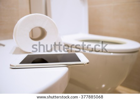 close up of toilet paper and a phone to work from the toilet - stock photo