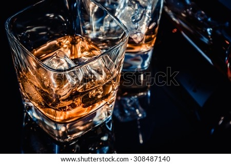 close-up of top of view of glass of whiskey near bottle on black table with reflection, time of relax with whisky, old style - stock photo