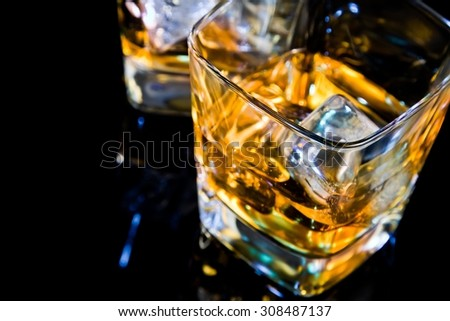 close-up of top of view of glass of whiskey on black table with reflection, time of relax with whisky