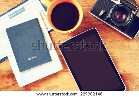 close up of top view image of tablet with empty screen, old camera passport and flight boarding pass. - stock photo