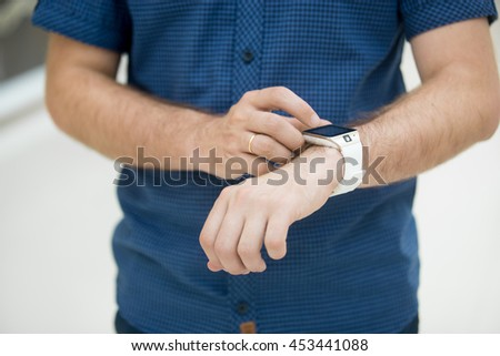 Close-up of torso of young man touching display on his smart watch, using internet, messaging, making call, or using app