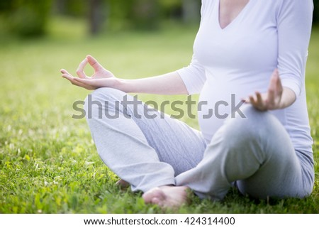 Close-up of torso of young pregnant model working out in park. Future mom sitting cross-legged in easy yoga pose on meditation session on grass lawn. Prenatal Yoga. Healthy maternity concept - stock photo