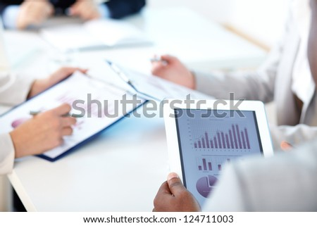 Close-up of touchpad in businessman hands during meeting