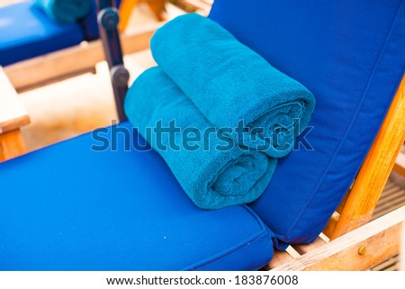Close-up of towels on the loungers near swimming pool - stock photo