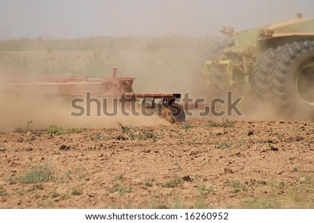 Close up of tractor pulling plow, throwing dust up in the air.