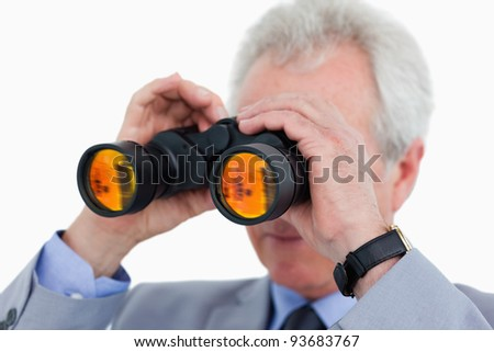 Close up of tradesman looking through binoculars against a white background - stock photo