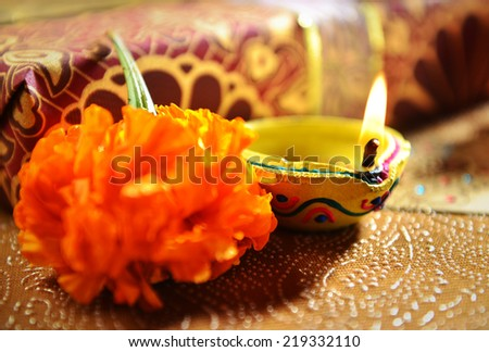 Close up of traditional indian oil lamp glowing against gift box background - stock photo