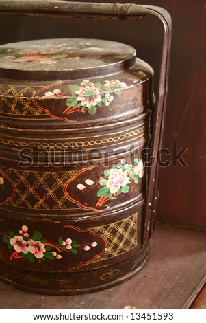 close up of traditional three storey tiffin carrier painted with flower motifs - stock photo
