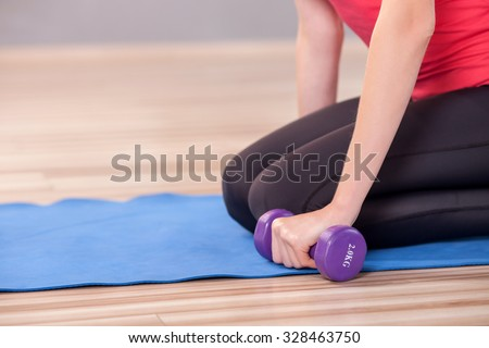 Close up of trained body of young woman exercising in gym. She is sitting on carpet and holding dumbbell - stock photo
