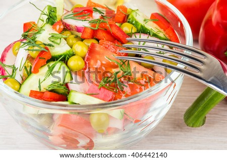 Close up of transparent bowl with vegetable salad and fork on wooden table