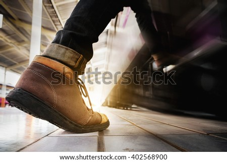 Close up of traveler feet step up to a passing train vintage tone. travel concept. - stock photo