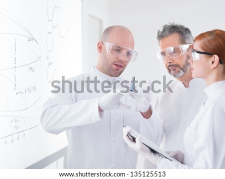 close-up of tree people in a chemistry lab preparing an injection with a whiteboard on the background