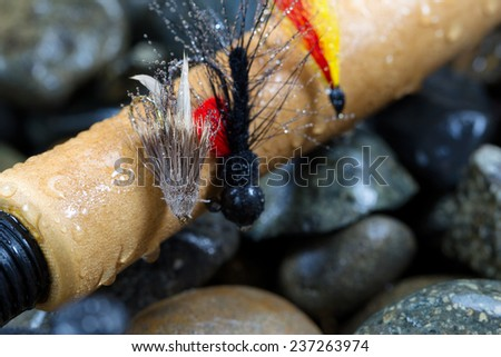 Close up of  trout flies, focus on front one with shallow depth of field, on wet cork handle of fishing rod with blurred out river rocks in background - stock photo