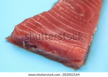 Close up of tuna steak on blue cutting board. - stock photo