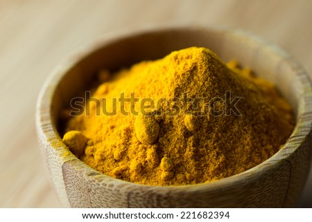Close up of turmeric powder in wooden bowl - stock photo