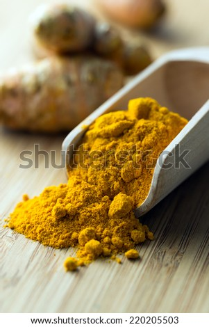 Close up of turmeric powder in wooden scoop