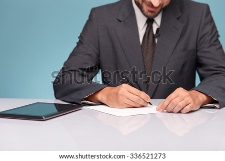 Close up of tv reporter sitting at the desk near a tablet. The man is writing down data into documents. He is smiling