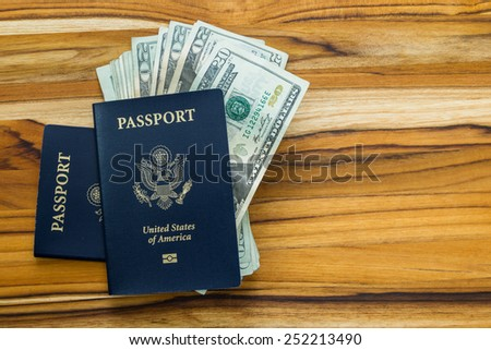 close up of two american passports and cash money on a wooden table for a travel concept - stock photo
