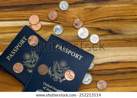 close up of two american passports and coins for a cheap travel concept - stock photo