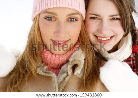Close up of two attractive girls friends with their arms around each others shoulders, being joyful and smiling with their heads together while wearing warm coats and jackets in winter. - stock photo