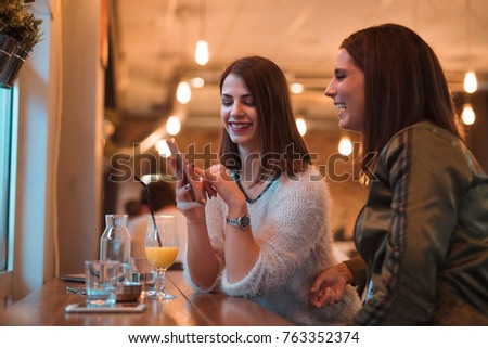 Close-up of two attractive girls while talking in cafe