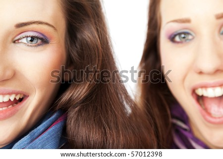 Close-up of two beautiful female half faces, laughing and looking at the camera - stock photo