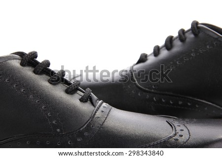 Close up of two black leather shoes crossing each other, isolated over white background - stock photo