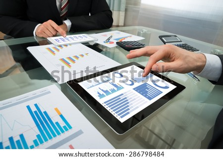 Close-up Of Two Businessman Analyzing Graph On Digital Tablet - stock photo