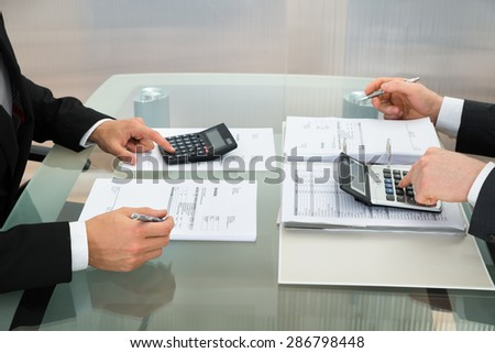 Close-up Of Two Businessman Calculating Documents Using Calculator In Office - stock photo