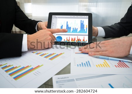 Close-up Of Two Businessman Discussing Graph On Digital Tablet At Workplace - stock photo