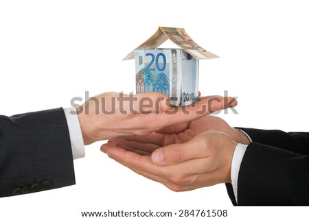 Close-up Of Two Businessman's Hand Holding House Made Of Euro Notes Over White Background - stock photo