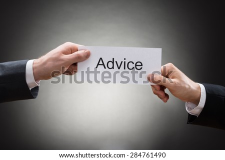 Close-up Of Two Businessman's Hand Holding Paper With Advice Word On It - stock photo
