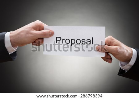 Close-up Of Two Businessman's Hand Holding Paper With Proposal On It - stock photo