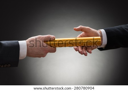 Close-up Of Two Businessman's Hand Passing A Golden Relay Baton - stock photo