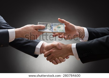 Close-up Of Two Businessmen Shaking Hands And Receiving Banknote - stock photo