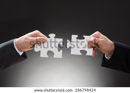 Close-up Of Two Businesspeople Connecting Jigsaw Puzzle Pieces - stock photo