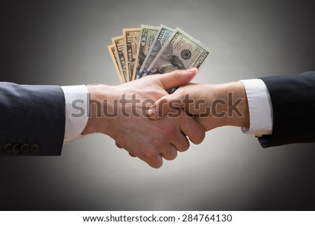 Close-up Of Two Businesspeople Shaking Hands With Money - stock photo