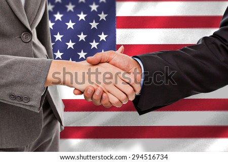Close up of two businesspeople shaking their hands against black wall