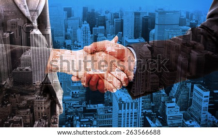 Close up of two businesspeople shaking their hands against high angle view of city - stock photo