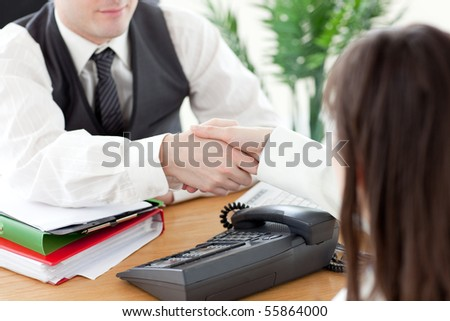 Close-up of two colleagues shaking hands in the office - stock photo