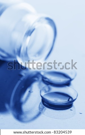 Close-up of two contact lenses with drops and glass bottle. Blue toned image.